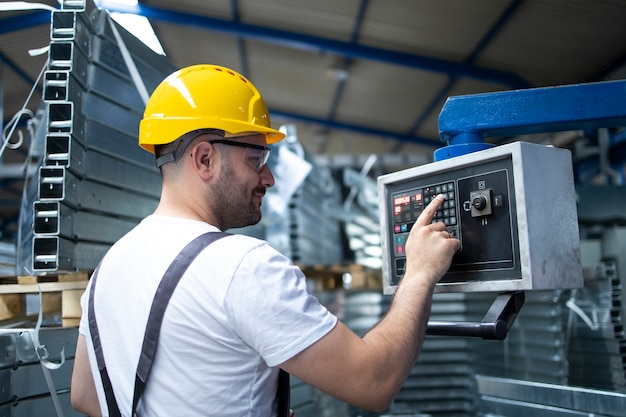 Trabalhador de fábrica operando máquina industrial e configurando parâmetros no computador