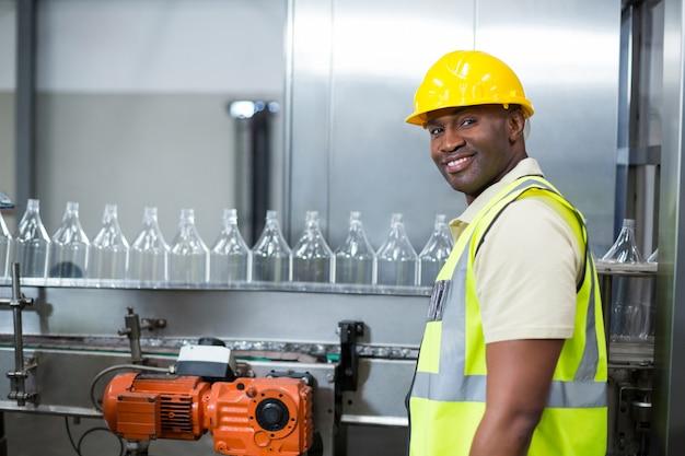 Trabalhador de fábrica sorridente ao lado de linha de produção