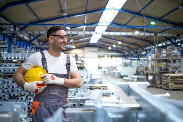 Trabalhador de fábrica sorridente com capacete em pé na linha de produção da fábrica