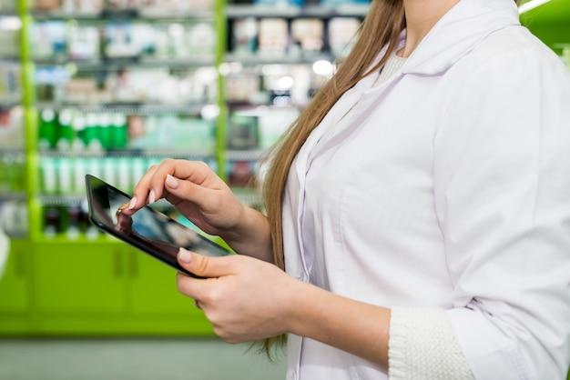 Trabalhador de farmácia verificando algo no tablet.