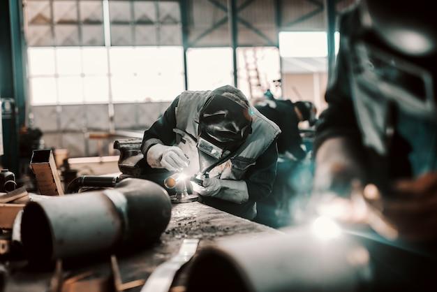 Trabalhador de ferro em traje de proteção, máscara e luvas de tubo de soldagem. interior da oficina.