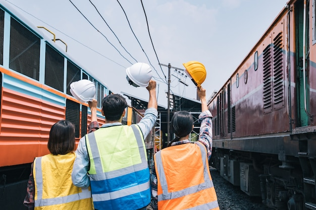 Trabalhador de grupo de engenheiros segurando capacete após finalizar grande projeto entre o intervalo dos trens