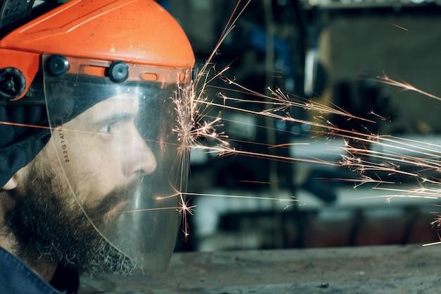 Trabalhador de homem com máscara protetora transparente funciona em metal com serra circular. faíscas e rosto.