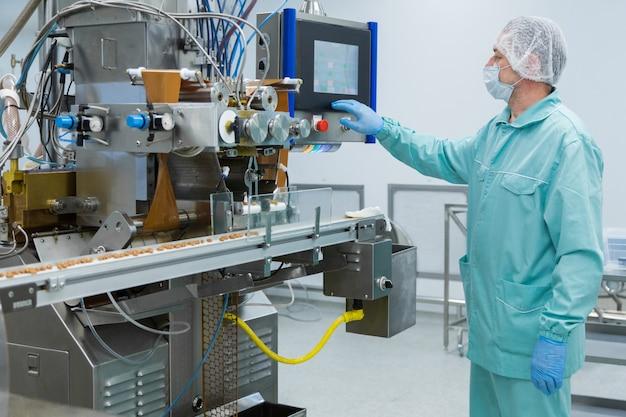 Trabalhador de homem de fábrica de indústria de farmácia em roupas de proteção em condições de trabalho estéril