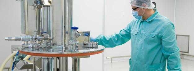 Trabalhador de homem de fábrica farmacêutica em roupas de proteção, trabalhando com painel de controle em condições de trabalho estéril