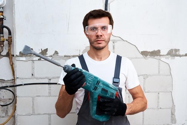 Trabalhador de homem usando furadeira, close-up. conceito de renovação