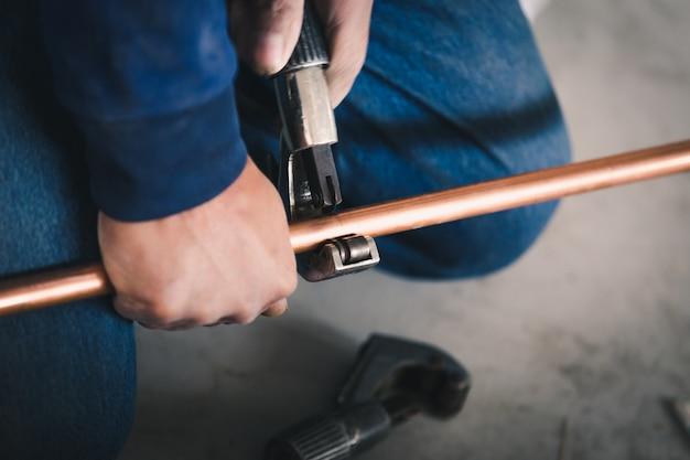 Trabalhador de homens de sistema de indústria corta a junta com a ferramenta do condicionador de ar de tubo de cobre