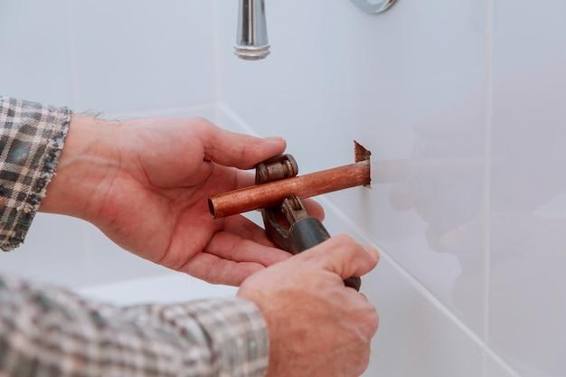 Trabalhador de homens de sistema de indústria corta a junta com a ferramenta do tubo de cobre