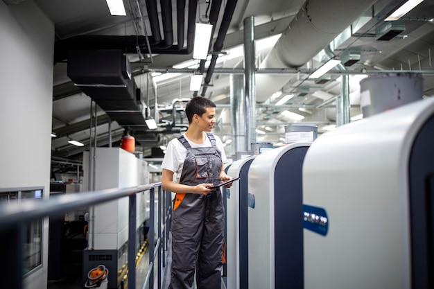Trabalhador de impressão feminino controlando o processo de impressão na máquina offset moderna na gráfica.