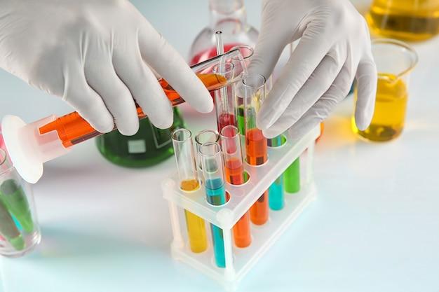 Trabalhador de laboratório despejando líquido laranja em um tubo de ensaio perto da mesa, close-up