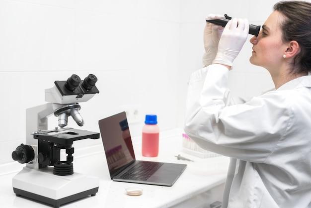 Trabalhador de laboratório judicial que estuda amostras com refractometer e microscópio, portátil na tabela, ciência forense.