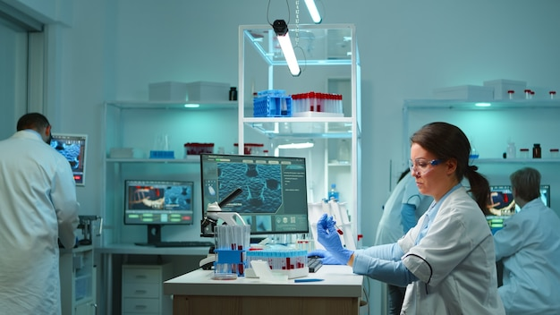 Trabalhador de laboratório médico analisando soro sanguíneo, realizando teste de vírus em um moderno laboratório equipado, tarde da noite. equipe de especialistas examinando a evolução da vacina usando alta tecnologia para tratamento contra covid19
