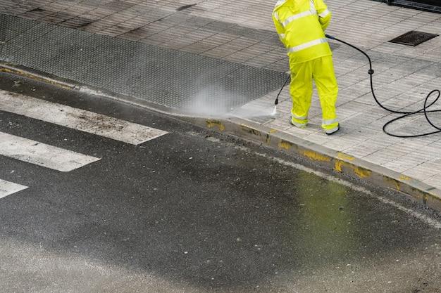 Trabalhador de limpeza da calçada com água pressurizada. conceito de manutenção ou limpeza