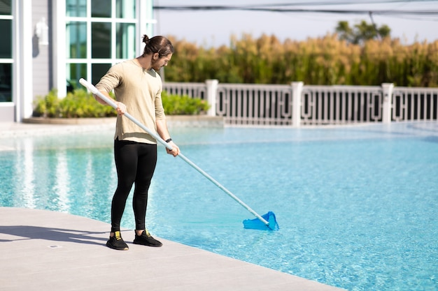 Trabalhador de limpeza profissional jovem limpando piscina com rede de colher ao ar livre.