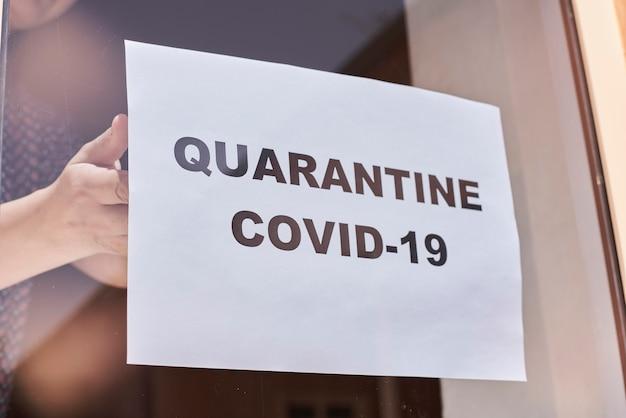 Trabalhador de loja ou restaurante pendurado um sinal de aviso