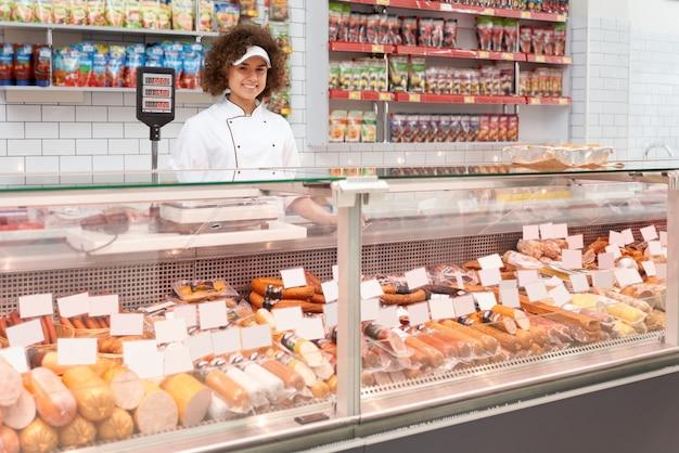 Trabalhador de loja posando atrás do balcão.