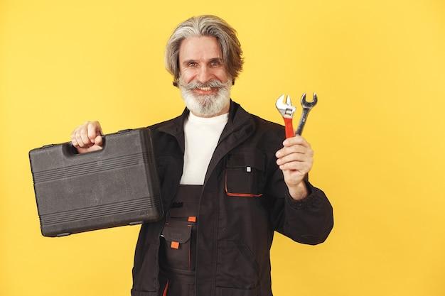 Trabalhador de macacão. homem com ferramentas. sênior com caixa.