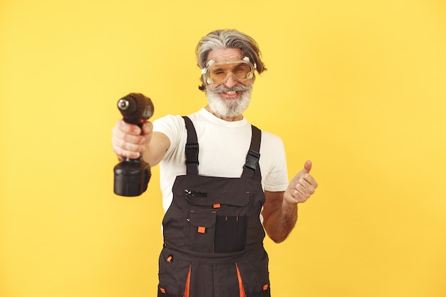 Trabalhador de macacão. homem com ferramentas. sênior com chave de fenda.