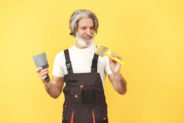 Trabalhador de macacão. homem com ferramentas. sênior com espátula.
