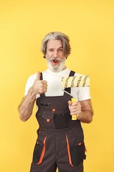 Trabalhador de macacão. homem com ferramentas. sênior com rolo de pintura.