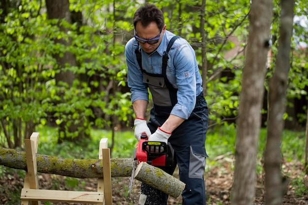 Trabalhador de macacão serra tronco de árvore com a motosserra em cavaletes na floresta
