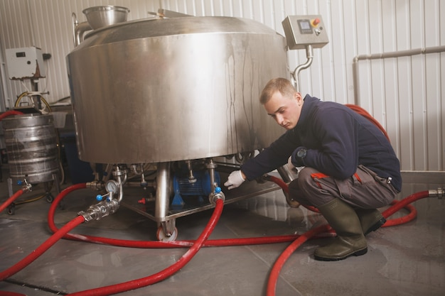 Trabalhador de manutenção examinando equipamento de microcervejaria