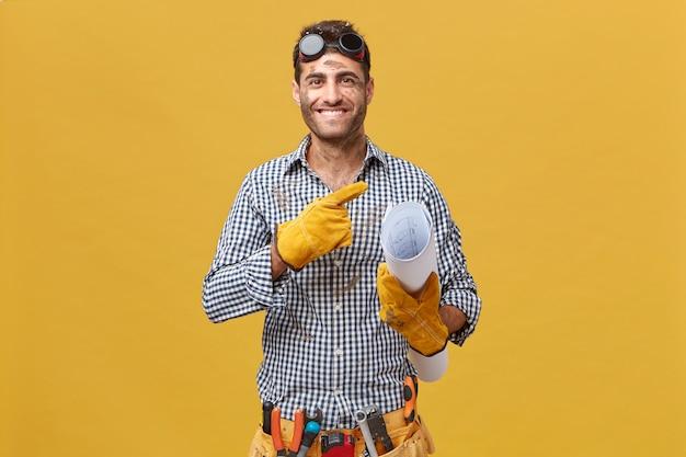 Trabalhador de manutenção feliz ou reparador com cara suja usando óculos de proteção, luvas e cinto com instrumentos segurando a planta em pé contra a parede em branco amarela apontando para copyspace