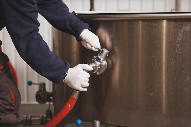 Trabalhador de manutenção irreconhecível verificando o tanque de cerveja na microcervejaria