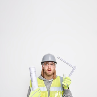 Trabalhador de manutenção segura fita métrica e projeto de papel usa uniforme de capacete protetor isolado no branco