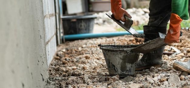 Trabalhador de mão closeup reboco cimento na parede para construção de casa