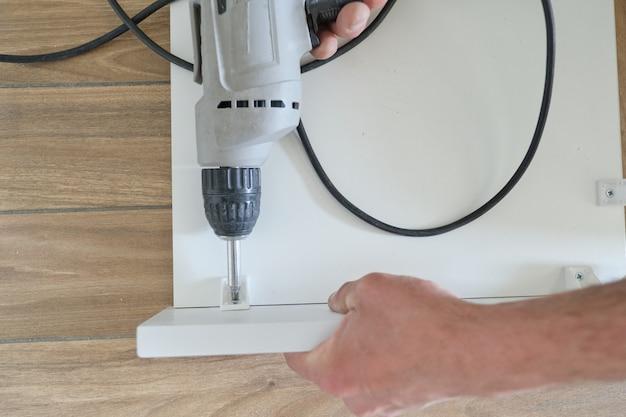 Trabalhador de mão fazendo móveis com ferramentas profissionais