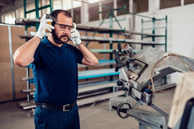 Trabalhador de máquina de corte de serra de fita colocando protetores de orelha
