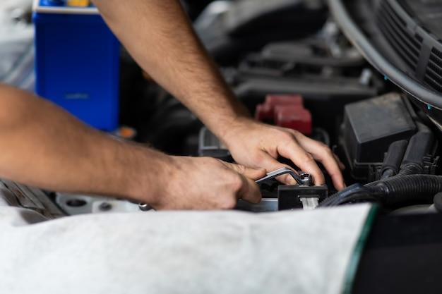 Trabalhador de mecânico de automóveis verificando e trocando a bateria do carro. manutenção do carro e conceito de garagem de serviço automático.