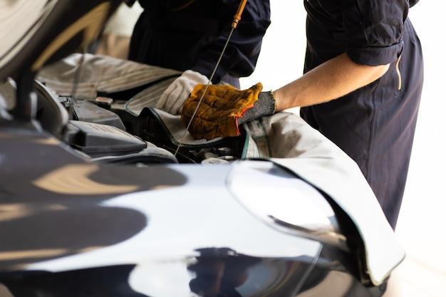 Trabalhador de mecânico de automóveis verificando o nível de óleo no motor do carro. manutenção do carro e conceito de garagem de serviço automático.