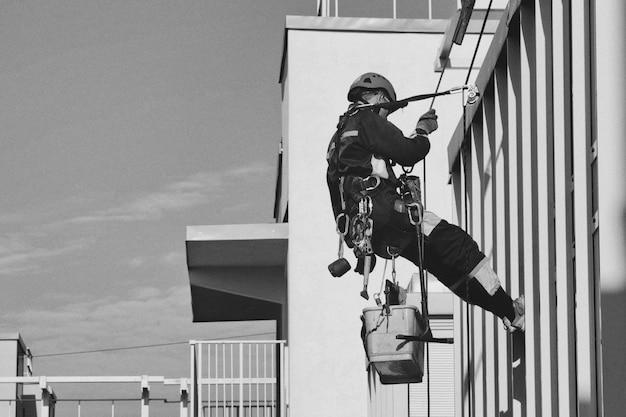 Trabalhador de montanhismo industrial paira sobre o prédio da fachada residencial enquanto lava o vidro da fachada externa. trabalhador de acesso por corda pendurado na parede da casa. conceito de obras urbanas. copie o espaço para o site