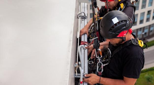 Trabalhador de montanhismo industrial paira sobre um prédio residencial durante a instalação