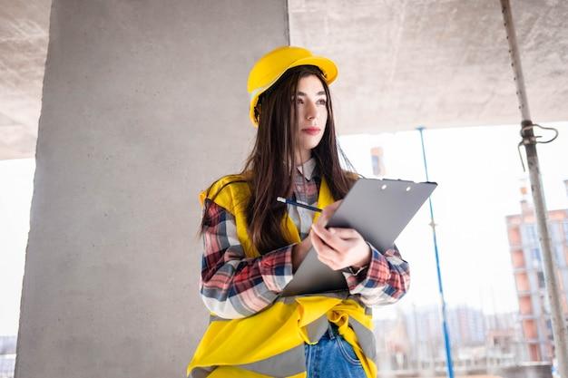 Trabalhador de mulher bonita inspeciona o fluxo de trabalho no canteiro de obras, preenchendo documentos