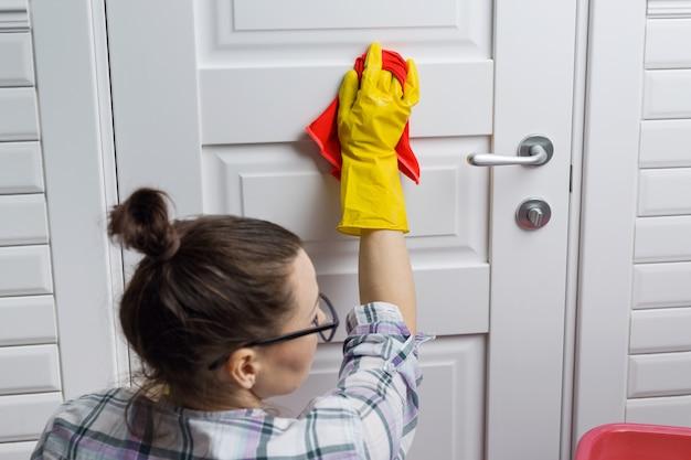 Trabalhador de mulher em luvas de borracha, fazendo a limpeza no banheiro