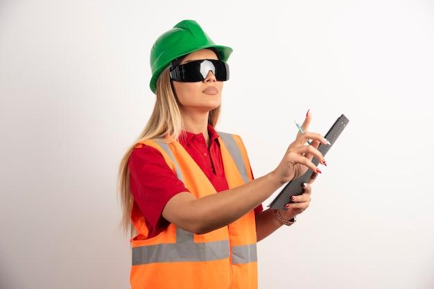 Trabalhador de mulher segurando um lápis com a prancheta.