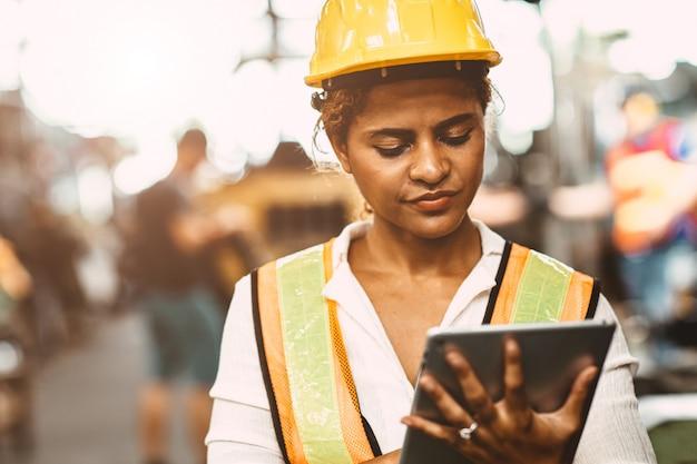 Trabalhador de mulheres americano no uniforme feliz vestindo e capacete da segurança do coordenador de manutenção da indústria pesada usando o tablet pc para verificar a máquina na fábrica.