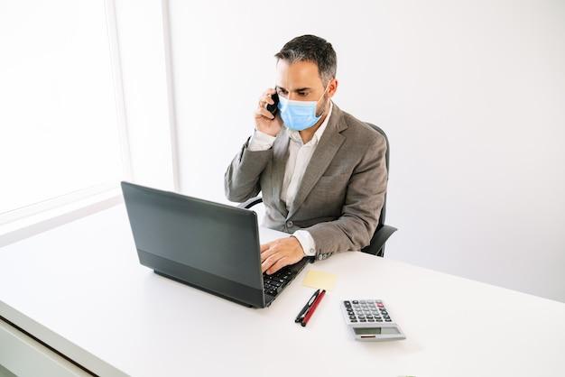 Trabalhador de negócios trabalhando e falando em um telefone celular com uma máscara facial devido à pandemia covid19 com um laptop, calculadora, telefone celular, postar, canetas, tudo com luz de fundo branca e área de trabalho