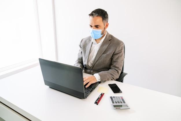 Trabalhador de negócios trabalhando em um laptop com uma máscara facial devido à pandemia de coronavírus covid19 com uma calculadora, telefone celular, post-it, canetas, tudo com luz de fundo branca e área de trabalho