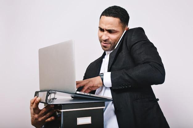 Trabalhador de oficce surpreso retrato segurando pastas, laptop falando no telefone. homem de negócios elegante, construindo carreira, gerente inteligente, trabalho moderno, mal-entendido.