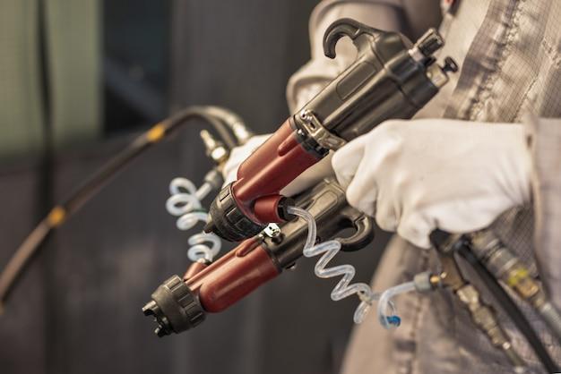 Trabalhador de oficina de pintura com pulverizadores industriais nas mãos