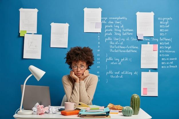 Trabalhador de pele escura chateado segura o queixo, senta-se à mesa perto do computador portátil analisa os resultados e sente-se cansado de trabalhar.
