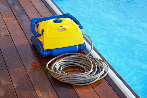 Trabalhador de pessoal do hotel limpando a piscina. limpadores de piscina automáticos.