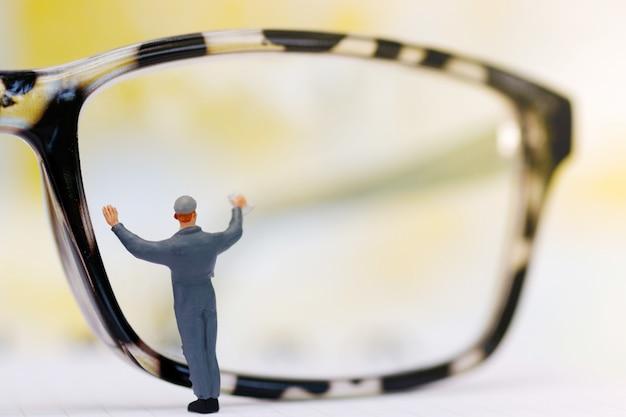 Trabalhador de pessoas em miniatura, limpeza de óculos de olhos. o negócio