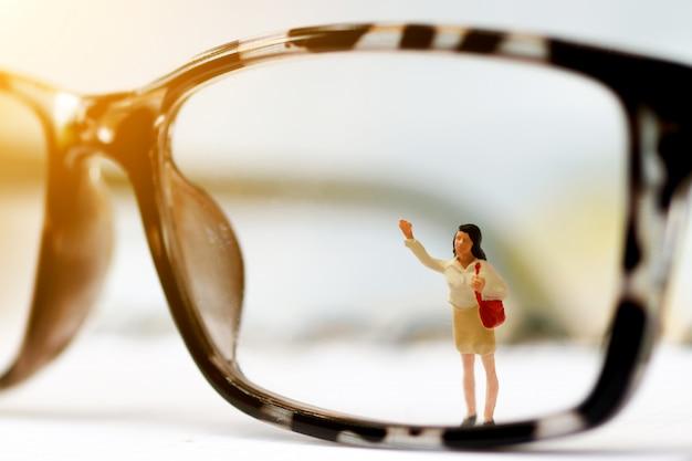 Trabalhador de pessoas em miniatura, limpeza de óculos de olhos.