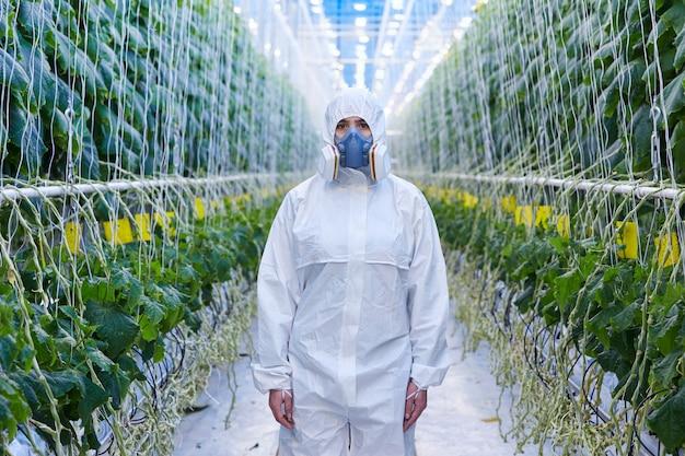 Trabalhador de plantação feminino em traje de hazmat