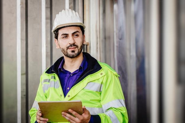 Trabalhador de raça latino-indiana bonito trabalhando em armazém de carga de fábrica industrial mão segurando lista de verificação parecendo esperto